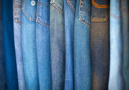 examine: Diverse shades of blue denim trousers, arrayed in an overlapping pattern for shoppers to examine.