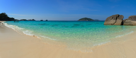blue waters: Crystal clear, tropical blue waters welcome tourists and excursionists on this sunny, white-sand beach in the Similan Islands of Thailand.