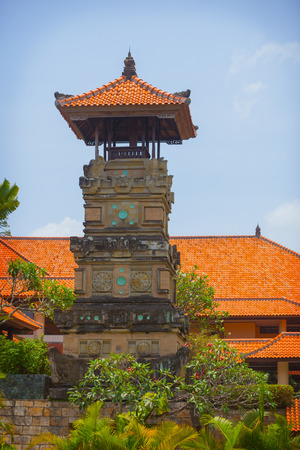 terra cotta: Red, terra cotta roof tiles cover a Buddhist temple and a pagoda tower in a garden in Southeast Asia. Stock Photo