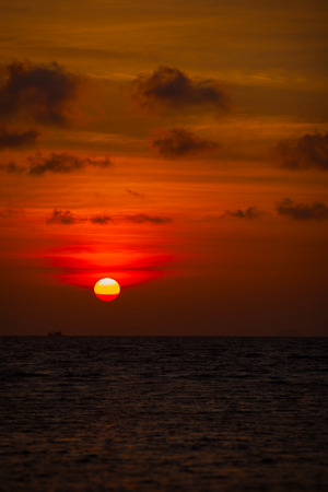 hazy: Red ball of the sun, setting slowly against the distant, hazy horizon, over a tropical sea.