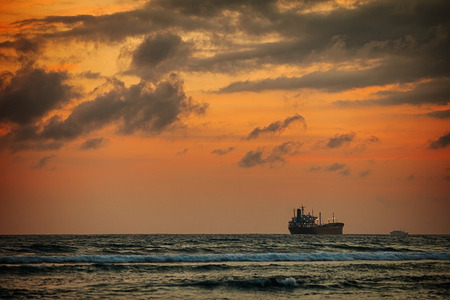 late summer: Enormous tanker ship, passing in the distance, along the horizon on this tropical sea at sunset.