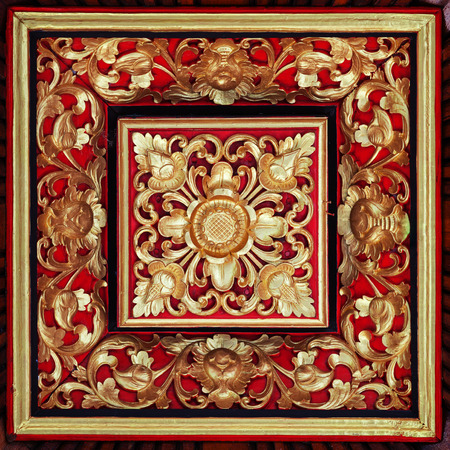 Beautiful and symetrical, hand carved relief with a floral motif, painted in red, gold and black.