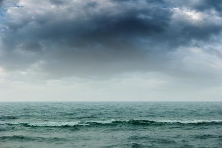 mare agitato: nubi temporalesche grigio sopra l'oceano blu rendendo mare mosso e un paesaggio marino drammatica. Archivio Fotografico