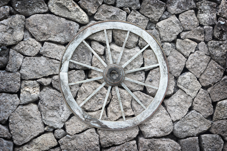 old wood farm wagon: Beautiful old-fashioned wooden wagon wheel set on a stone wall.