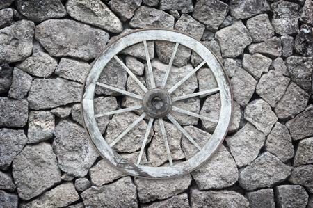 carreta madera: rueda pasada de moda hermosa carro de madera fijado en un muro de piedra.