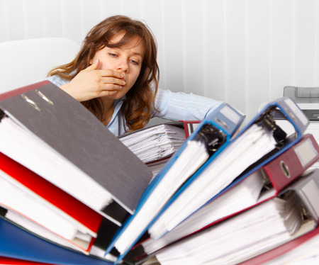 bookkeeping: Young female accountant. Attractive and tired, over worked with too much book keeping to do.