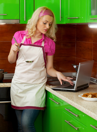 A modern young attractive female wearing jeans and an aprin the kitchen using her laptop on the bench. photo