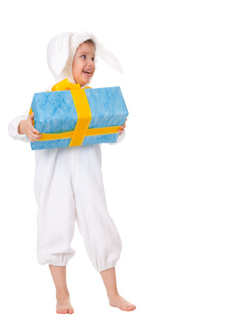 costum: Young boy in an Easter bunny costum holding a gift with blue wrapping paper and a gold ribbon. Stock Photo