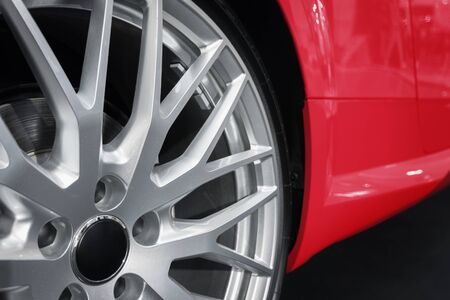 custom car: Closeup of a custom wheel rim with matte finish, visible lug nuts and racing tires, mounted on red, luxury sports car.