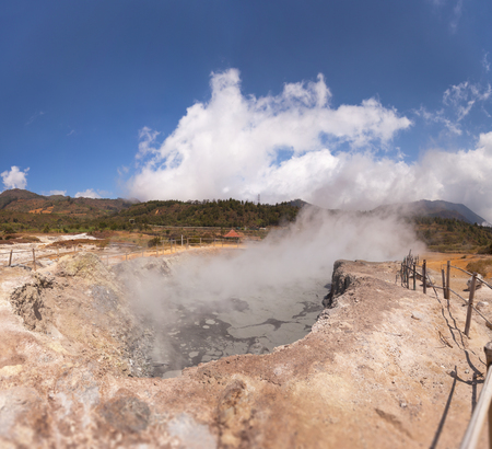 heated: Steam rises from a natural, geothermally heated geyser in Java, Indonesia, under a deep, blue sky. Stock Photo