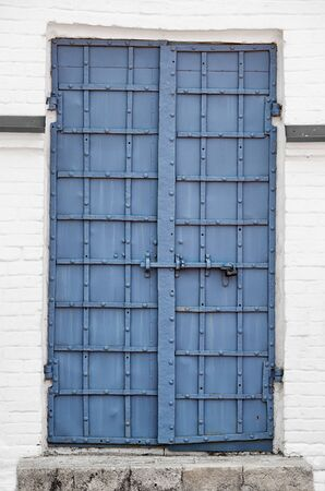 iron barred: Black painted, reinforced iron door, held together with rivets and barred shut with a security bolt, at the entrance to an old building. Stock Photo