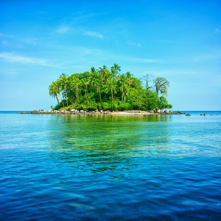 castaway: Tropical atoll giving off a reflection on the tranquil water.