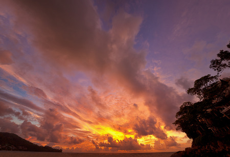 majestic: Dramatic sunset, sunrise with gold warm colored clouds over the ocean and head land.