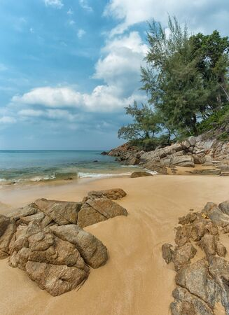 partly: Massive boulders, partly burried in the coarse sand, on a beautiful, tropical beach paradise on the Island of Phuket, in Thailand.
