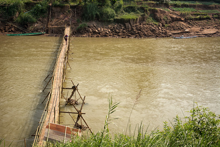 decrepit: Luang Prabang, Laos - Decrepit bridge from bamboo across the river. Green grass and boats on the shore Stock Photo