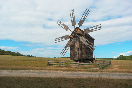 Ukraine, Kiev, Pirogovo. Ancient windmill on the field. blue sky background