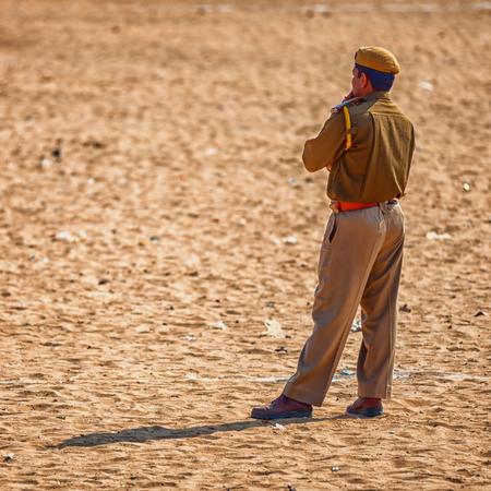 jailer: PUSHKAR, RAJASTHAN, INDIA - CIRCA NOV 2012: Traditional Fair in Pushkar. A police officer keeps order Editorial