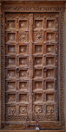 dilapidated wall: Jaisalmer, Rajasthan, India. Old crooked wooden door. The usual entrance to the town house