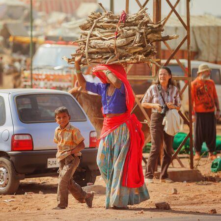 miserable: PUSHKAR, RAJASTHAN, INDIA - CIRCA NOV 2012: Traditional Fair in Pushkar. Woman carries a bundle of firewood