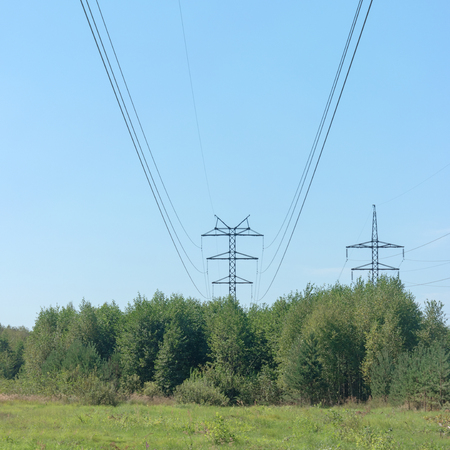 over voltage: Electrical wires on steel supports. High-voltage power line over the forest