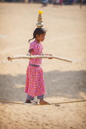 feats: PUSHKAR, RAJASTHAN, INDIA - CIRCA NOV 2012: Child Circus Entertainer Performs on a Tightrope in Pushkar Editorial
