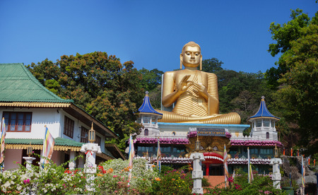 Enormous, gilded Buddha sculpture in a seated position, presiding over the Dambulla Cave Temple in central Sri Lanka. Stock Photo