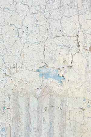 The surface of the wall covered with old damaged paint. Vertical background