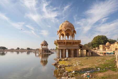 Ornate, intricately carved dome structures of Gadi Sagar Temple, on Gadisar Lake in Jaisalmer, Rajasthan, India. Stock Photo