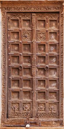 Jaisalmer, Rajasthan, Indien. Alte krumme Holztür. Der übliche Eingang zum Stadthaus Standard-Bild - 86805124