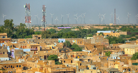 Jaisalmer, Rajasthan, Indien. Straßen mit Mobilfunkmasten und Windkraftgeneratoren im Hintergrund Standard-Bild - 86945107