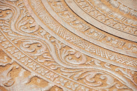 Closeup of intricate, symbolic carvings on the surface of a moonstone at a temple in Anuradhapura, Sri Lanka.