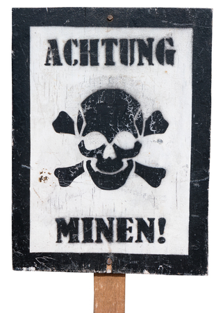 Antique wooden sign, isolated against a white background, in German language and with a skull and crossbones warning of landmines. Stock Photo