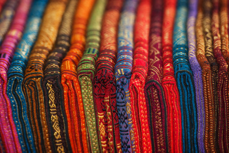 Row of carefully displayed, brightly colored silk scarves, inside a shop in Luang Prabang, Laos.
