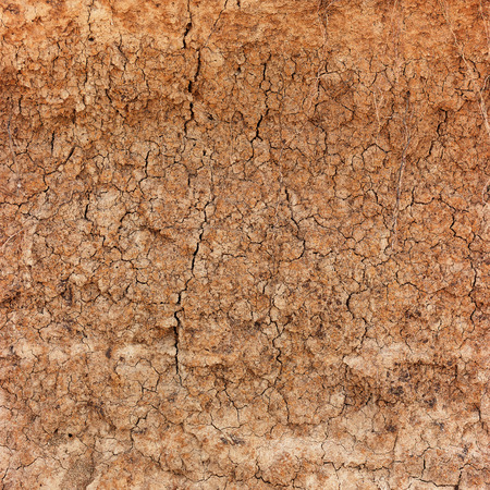 Extreme closeup of reddish, clay soil, cracking, crumbling and eroding under very dry conditions. Stock Photo