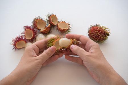 Peeling rambutan fruits by hands Stok Fotoğraf