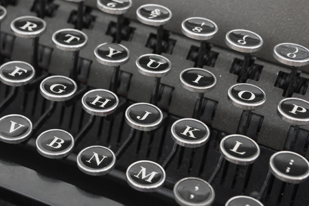 The keyboard of old typewriter. Black letters on the typewriter. Detail of a black vintage typewriter