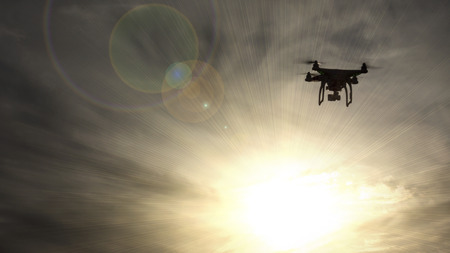 A UAV Drone silhouetted against the sun.