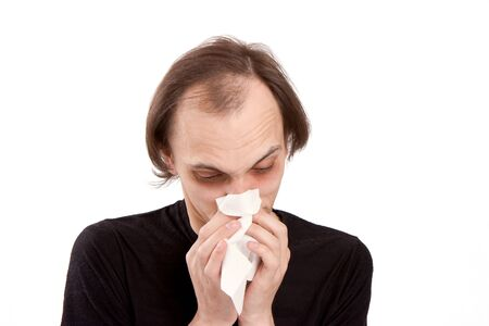 The man sneezes in a white paper handkerchief Stock Photo - 5213675