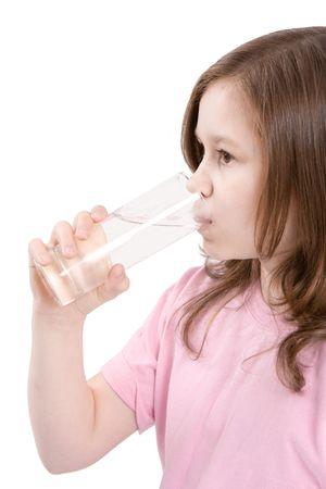 Das Mädchen trinkt Wasser aus einem transparenten Glas