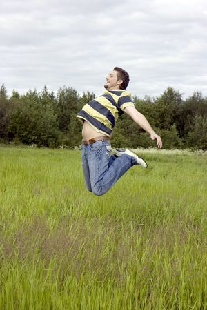 joyfully: The young man joyfully jumps on a grass