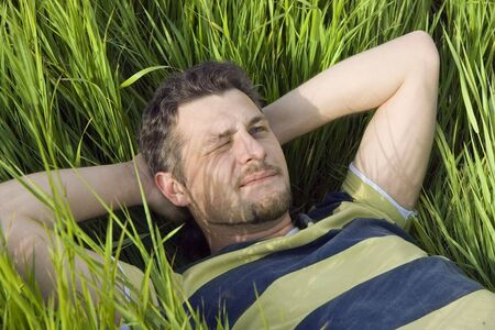 The man lies on a grass having screwed up one eye photo