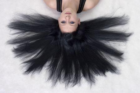 床に横たわって長い黒髪の少女 写真素材