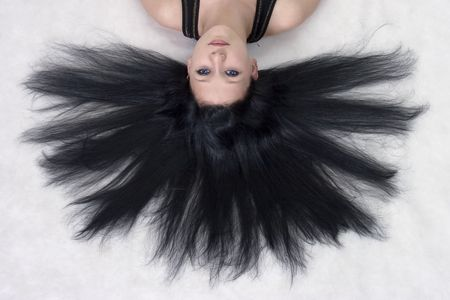 The girl with long black hair lying on a floor Stock Photo