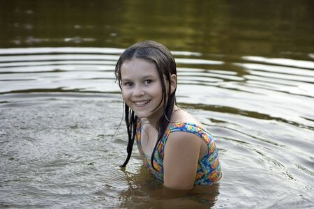 wet lips: The girl with wet hair sits on a belt in water and smiles