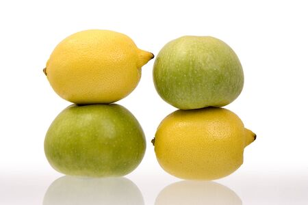 antipode: Two lemons and two green apples on a white background