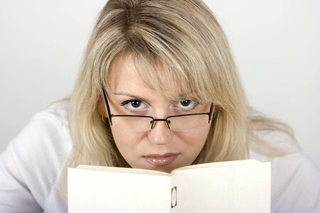 On a light background the girl in eyeglasses hides behind the book photo