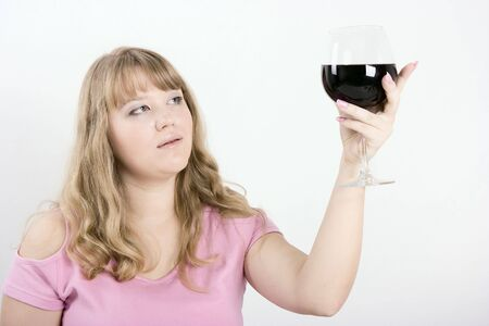 The young woman in a profile holds the big glass with wine photo