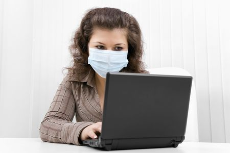 The young woman at office in medical mask works with the laptop photo