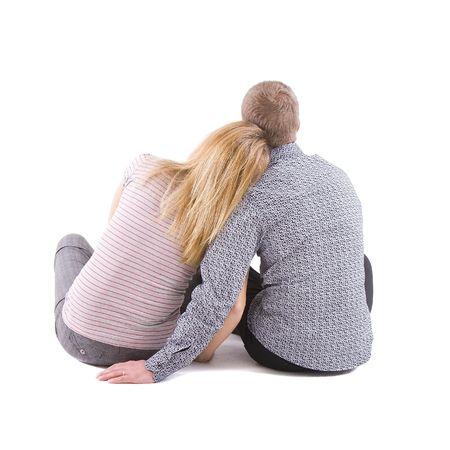 mujeres sentadas: Dos j�venes se sientan sobre fondo blanco vuelve a la c�mara