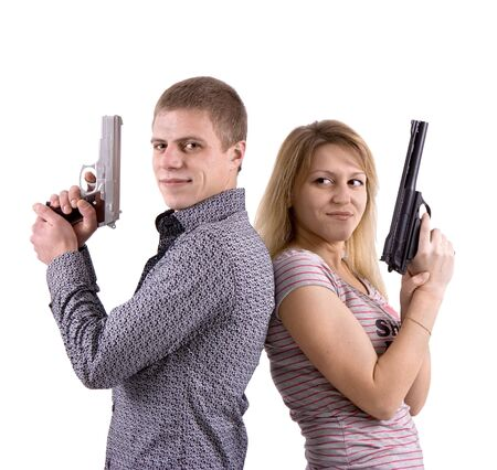 young man and woman standing back to back with the pistols in their hands photo